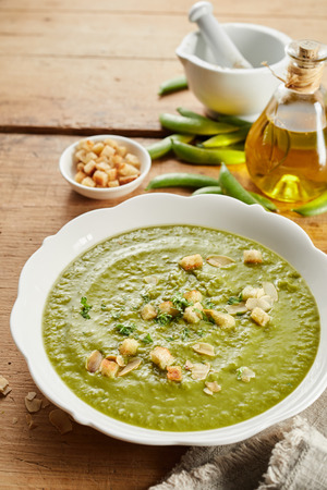 Homemade pea soup with roasted almonds and crunchy toasted bread croutons garnished with herbs viewed high angle on a rustic table