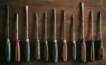 Neat row of old worn vintage screwdrivers with wooden handles on a rustic wood background panorama banner 写真素材