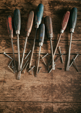 Old vintage screwdrivers with wooden handles arranged in a line as a top border on rustic wood with copy space and an assortments of screws Reklamní fotografie