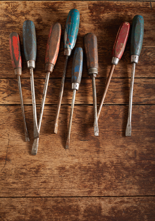 Set of old vintage wooden handled screwdrivers arranged in a row as an upper border on rustic wood with copy space Reklamní fotografie