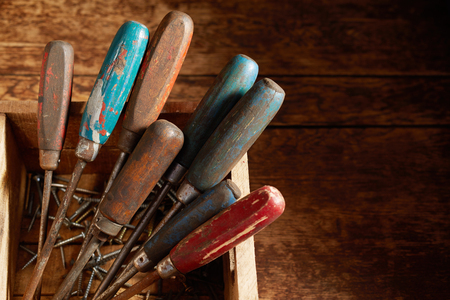 Wooden handles of old vintage screwdrivers propped upright in a wooden crate with loose screws in the bottom over a rustic table or workbench viewed high angle