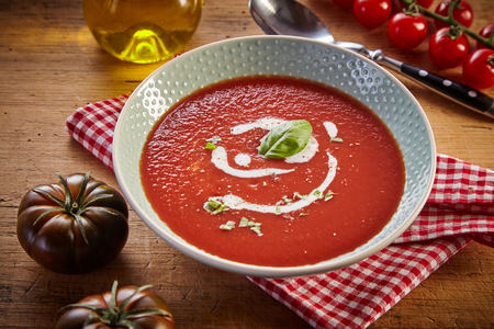 Plate of red tomato cream soup in rustic kitchen, served on checked napkin with greens and white sauce. Fresh and healthy organic food concept Stock Photo