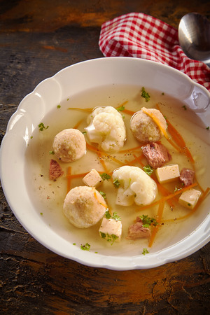 Bowl of spring broth with bone marrow dumplings, fresh vegetables and herbs viewed high angle on a rustic table for advertising Banco de Imagens - 119404185