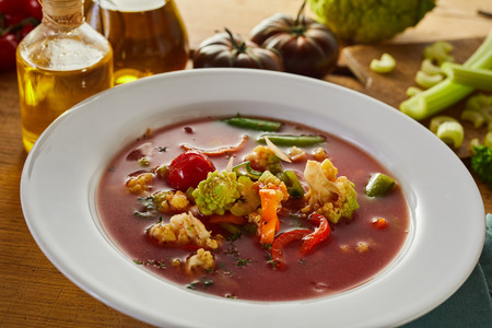 Italian minestrone soup with assorted fresh vegetables including celery, tomato, carrot and cauliflower in a rich broth