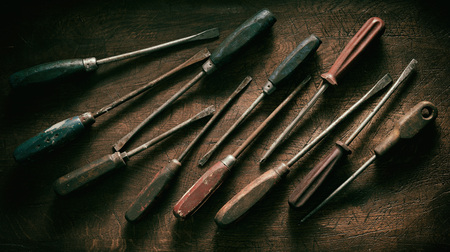 Panorama banner of old worn dirty vintage wooden screwdrivers arranged as a flat lay still life on wood with dark vignette