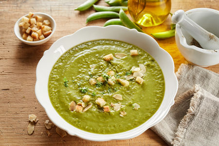 Bowl of thick pea soup served with sauteed croutons, flaked almonds and sprinkled with herbs viewed hogh angle with fresh ingredients and olive oil
