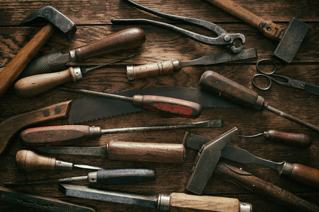 Woodworking background with vintage hand tools in a flat lay full frame view with screwdrivers, hand saw, snips, hammer and mallets Reklamní fotografie