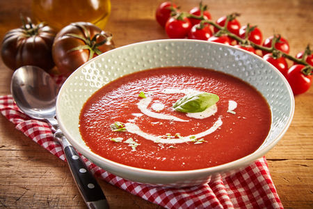 Plate of tomato cream soup with greens, served on red checked napkin on wooden table. Different kinds of tomatoes and jar of oil in background Stock Photo