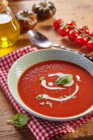White plate of red tomato cream soup with white sauce and herbs, served on checked napkin. Rustic kitchen concept with fresh tomatoes and jar of oil Stock Photo