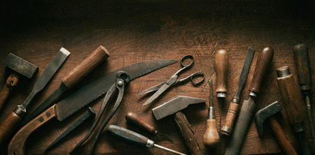 Dark moody arrangement of vintage hand tools with wooden handles for carpentry and woodworking in a panorama banner with copy space