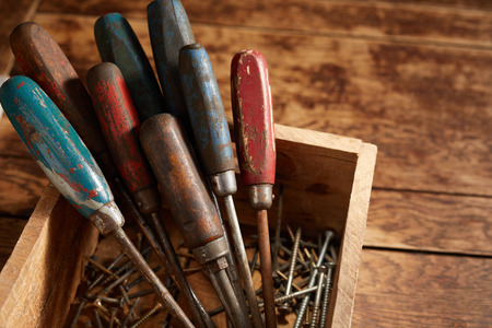Set of old vintage screwdrivers with worn wooden handles standing upright in a wooden crate with assorted crews in the bottom on a rustic table 写真素材