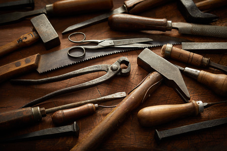 Wood handled vintage hand tools in a full frame view arranged neatly on a rustic wooden workbench with dark vignette