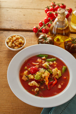 Bowl of delicious Italian minestrone soup with fresh vegetable ingredients and olive oil behind sevred with crunchy croutons, high angle vertical view