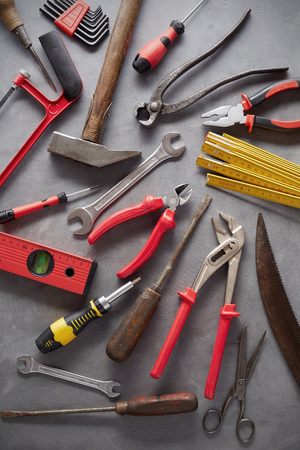 Flat lay still life of assorted old vintage and modern hand tools arranged on grey for woodworking and construction Reklamní fotografie