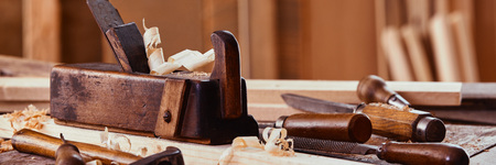 Panorama banner of vintage woodworking tools on a workbench with fresh shavings and sawdust in a low angle view Stock Photo
