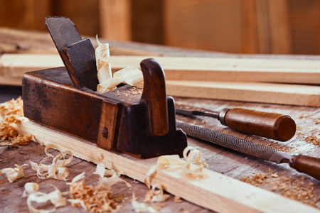 Vintage wooden plane on a plank of wood surrounded with shavings from smoothing the surface with a rasp, file and lumber on a workbench