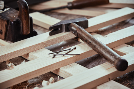 Old hammer and nails on criss-crossed planks of freshly planed wood on a workbench