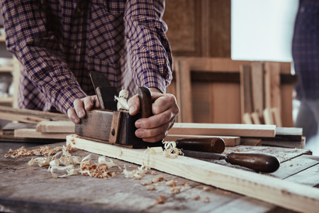 Carpenter or woodworker using an old wooden plane to smooth the surface of planks of fresh lumber in a woodworking workshop