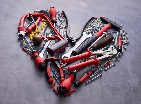 Herzförmige Anordnung von verschiedenen roten Handwerkzeugen für die Holzbearbeitung auf einem strukturierten Grau in Nahaufnahme Standard-Bild