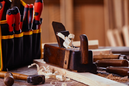 Old vintage plane with modern screwdriver set on a woodworking workbench with assorted hand tools in a close up low angle view