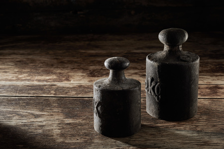 Two old antique metal kilogram weights placed in the corner on rustic wooden table for measuring and counterbalance on a scale
