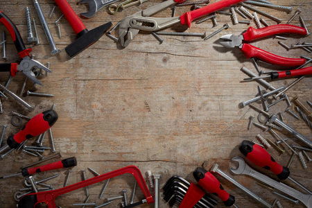 Colorful red hand tools in a DIY or renovations frame with scattered screws around central copy space on rustic weathered wood 写真素材