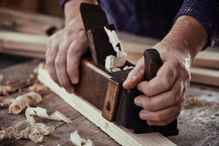 Hands of a carpenter, woodworker or joiner using a vintage plane to smooth the surface of a plank of lumber on his workbench Reklamní fotografie