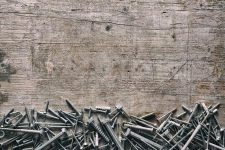 Verschiedene Gewindeschrauben bilden einen unteren Rand auf altem Vintage-Holz mit Kopierraum