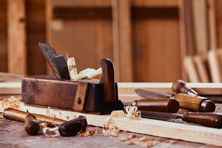 Old vintage woodworking plane with a plank of freshly planed wood and shavings on a workbench in a workshop