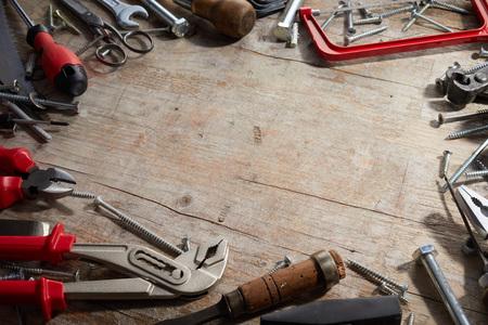 Verschiedene Vintage- und moderne Handwerkzeuge in einem Rahmen um den zentralen Kopierraum auf altem, rissigem rustikalem Holz in einem konzeptionellen Bild