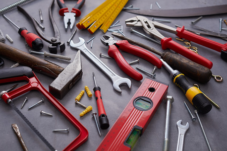 Assorted colorful red hand tools for building and construction mixed with a vintage hand saw, snips and mallet on grey viewed full frame high angle