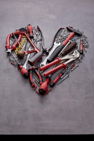 Heart-shaped still life of colorful red hand tools for woodworking and household DIY on a textured grey  with copy space below