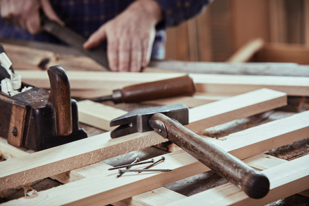 Carpenter working in his workshop with freshly planed planks with old hand tools and nails in the foreground