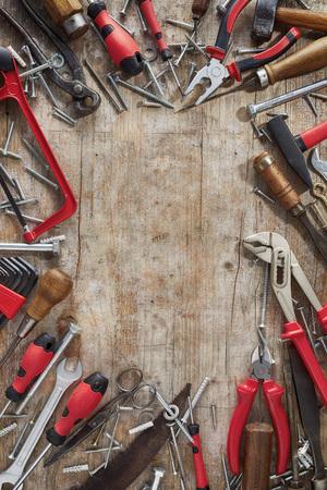 DIY-Grenze aus verschiedenen modernen roten und Vintage-Handwerkzeugen mit Schrauben auf rustikalem, rissigem Holz mit zentralem Kopierraum Standard-Bild
