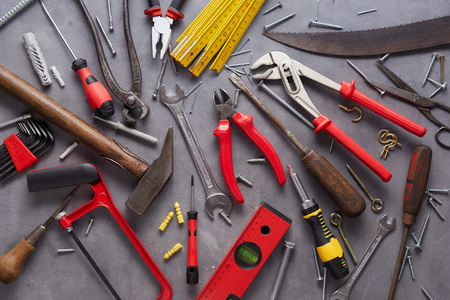 Variety of old vintage and modern household hand tools arranged as a flat lay still life on grey in a DIY and renovations concept Stock Photo