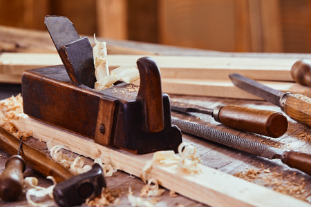 Wooden plane with rasp, file, hammer and chisels on a workbench with freshly planed planks of wood in a woodworking workshop