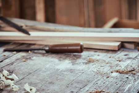 Woodworking  concept with copy space with a low angle view of a workbench with shavings, sawdust, scattered hand tools and planks of fresh wood or lumber