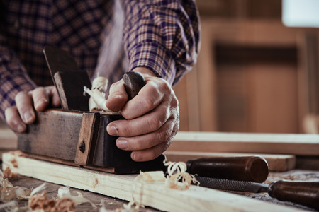 Carpenter or joiner planing a plank of wood smoothing the surface in a close up view on his hands and the tool on a workbench Reklamní fotografie