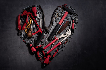 Flat lay heart-shaped still life of household DIY tools with colorful red handles on a dark grey  with copy space