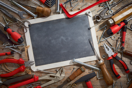 Assorted vintage and new tools in a frame surrounding on old chalkboard or school slate with copy space viewed from above 写真素材
