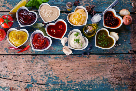 Large variety of marinades, sauces, herbs and spices with a decanter of olive oil in individual heart shaped bowls on a rustic wood background with copy space, top down view Stock Photo