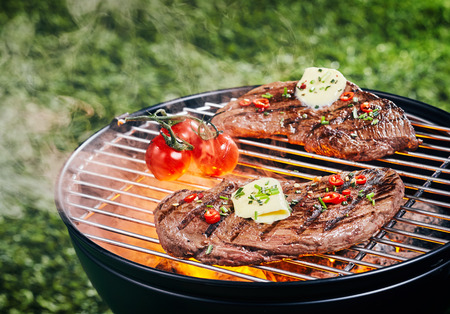 Two tender portions of rump steak grilling on a barbecue fire at a picnic or campsite garnished with herbs, spices and a curl of butter Stock Photo