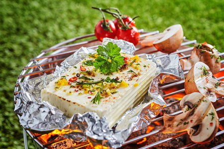 Portion of halloumi or tofu in aluminium foil grilling over the fire on a barbecue with fresh sliced mushrooms and tomatoes outdoors on green grass Banco de Imagens