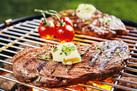 Succulent portion of rump steak grilling on a hot BBQ fire garnished with a curl of butter and fresh herbs Stock Photo
