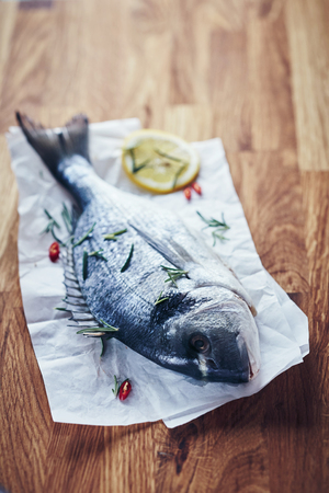 Whole fresh raw fish ready for grilling or baking seasoned with chili pepper and fresh herbs on a crumpled piece of white paper on a wooden kitchen table Stock fotó