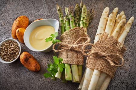 Ingredients for a gourmet asparagus appetizer with bundles of fresh white and green spears, mayonnaise, new potatoes and peppercorns