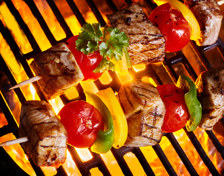 Delicious bbq kebab skewers on fire grilling on grid. Meat and vegetables on wooden stick skewers viewed from above Stock Photo