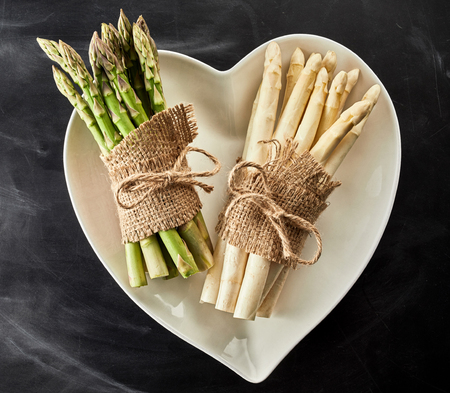 Heart shaped bowl with two bundles of white and green fresh asparagus spears tied with string and hessian over a slate background in square format