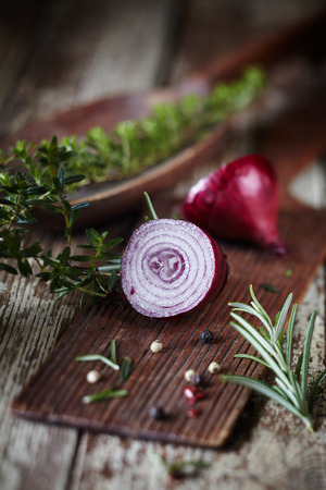 Sliced fresh raw red onion with herbs and peppercorns on an old vintage rustic wooden board on a kitchen table ready for cooking