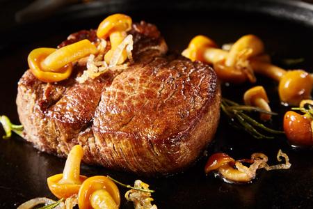 Gourmet gegrilltes Wildfleischsteak mit Pilzen, Kräutern und Zwiebeln in Nahaufnahme, geeignet für Menüwerbung für ein Restaurant